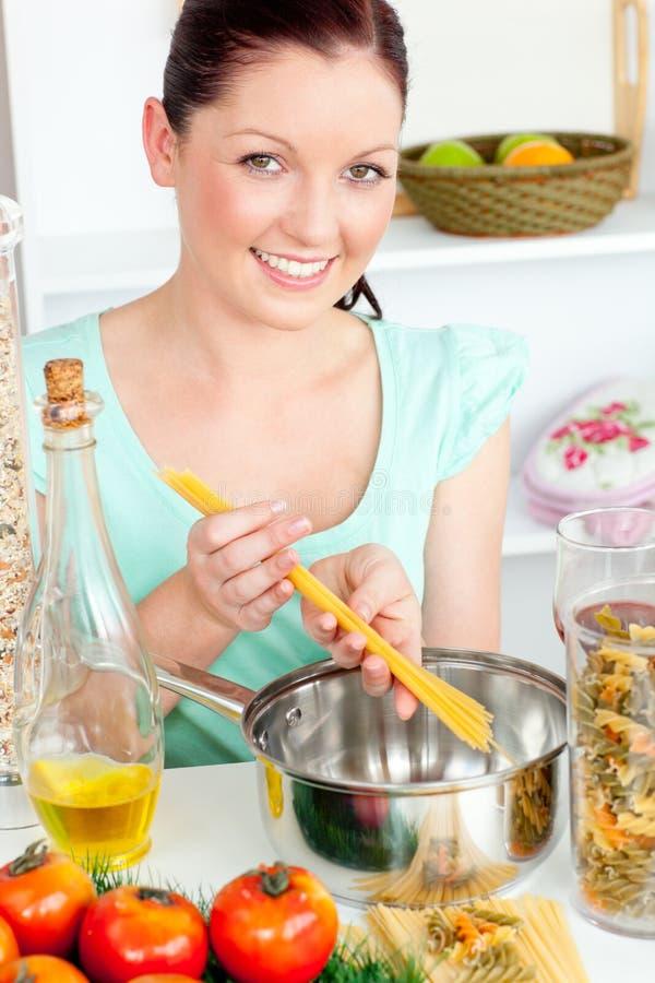 Mulher Charming que cozinha o espaguete na cozinha imagem de stock