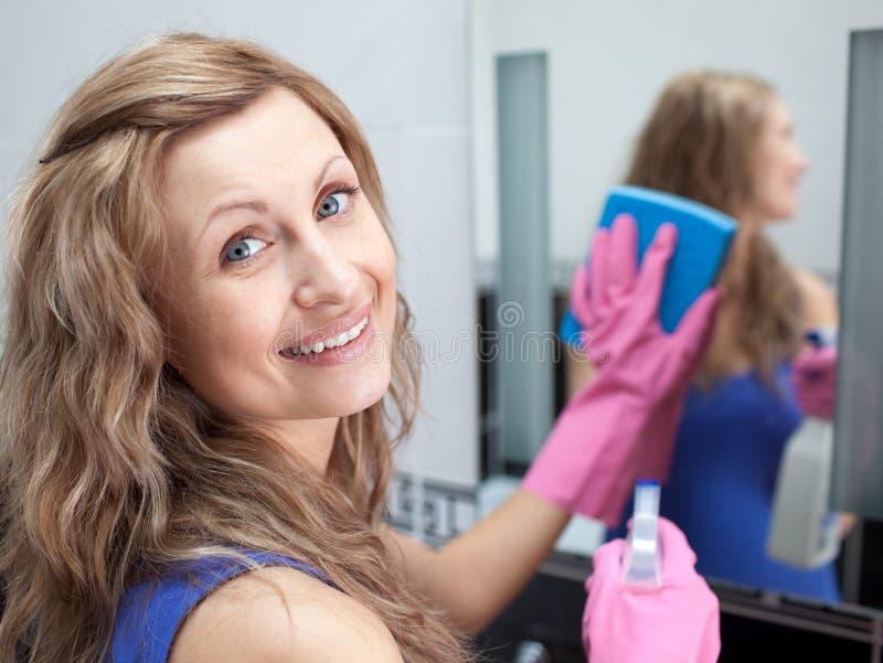 Mulher Charming que limpa o espelho de um banheiro imagem de stock