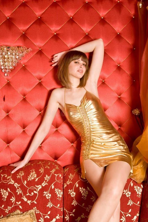 Mulher Charming que senta-se no sofá vermelho fotografia de stock royalty free