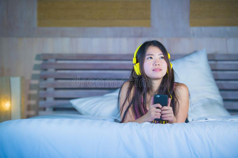 Mulher chinesa asiática atrativa e feliz nova com fones de ouvido amarelos que escuta a música no telefone celular na cama em cas foto de stock royalty free