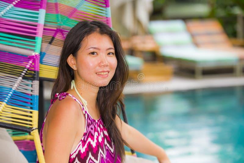 Mulher chinesa asiática bonita e feliz nova do turista que relaxa na piscina tropical do recurso luxuoso que senta-se no balanço  imagem de stock