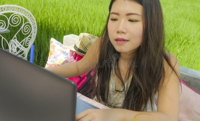 Mulher chinesa asiática bonita e feliz nova que trabalha fora com o café do fundo da grama verde dos trabalhos em rede do laptop  fotos de stock