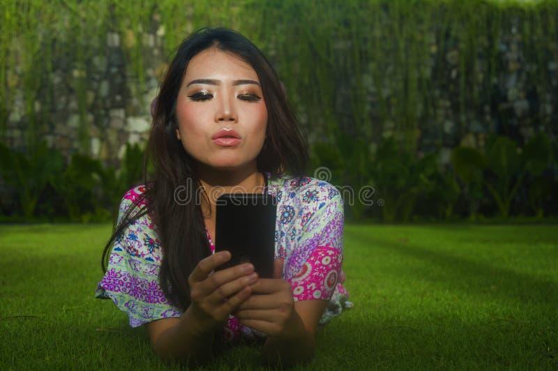 Mulher chinesa asiática bonita e lindo atrativa nova que encontra-se no parque da grama verde usando os meios sociais app do Inte imagens de stock royalty free