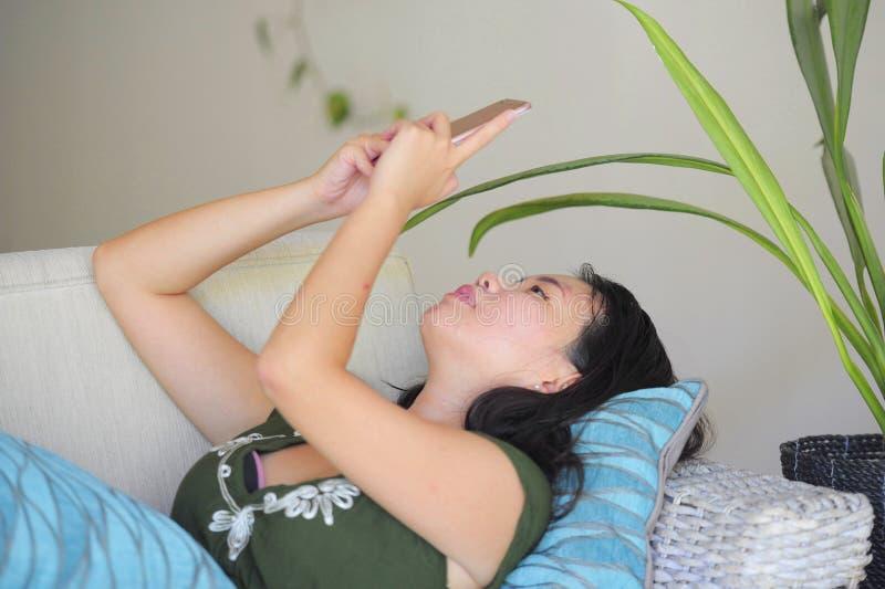 Mulher chinesa asiática bonita e relaxado nova que encontra-se em casa sofá do sofá da sala de visitas usando o Internet no telef fotos de stock