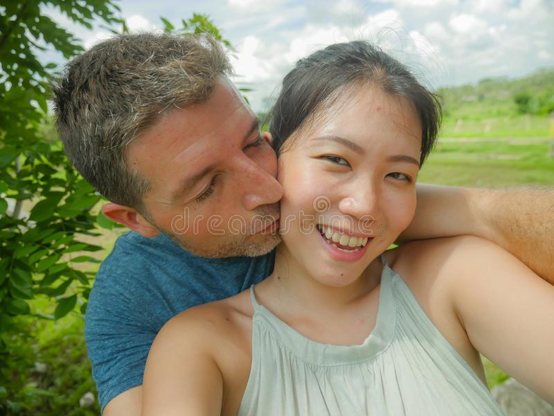 Mulher chinesa asiática bonita nova dos pares misturados bonitos e felizes da afiliação étnica e homem branco no amor que toma a  fotografia de stock