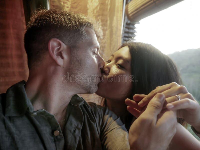 A mulher chinesa asiática dos pares misturados bonitos da afiliação étnica e o manin caucasiano amam beijar e comemorar a propost foto de stock