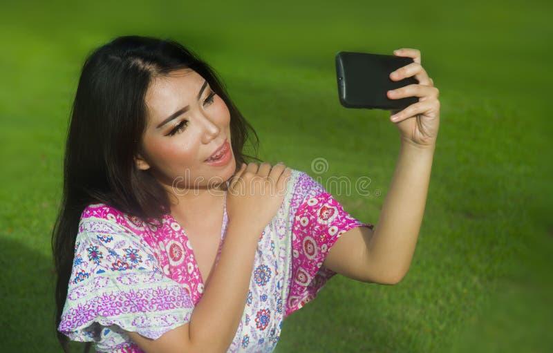 Mulher chinesa asiática feliz e bonita nova que toma o PIC do selfie com a câmera do telefone celular que levanta o ar livre sens fotografia de stock