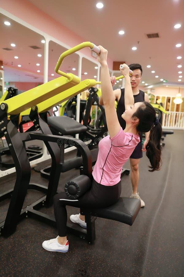 Mulher chinesa asiática na força do treinamento da mulher do esporte de ŒFitness do ¼ do ï do gym no gym fotografia de stock