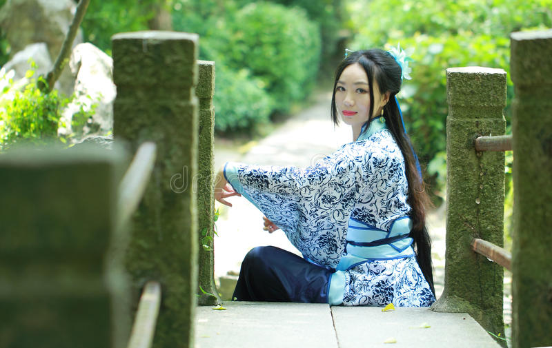 A mulher chinesa asiática no vestido azul e branco tradicional de Hanfu, jogo em um jardim famoso, senta-se na ponte foto de stock
