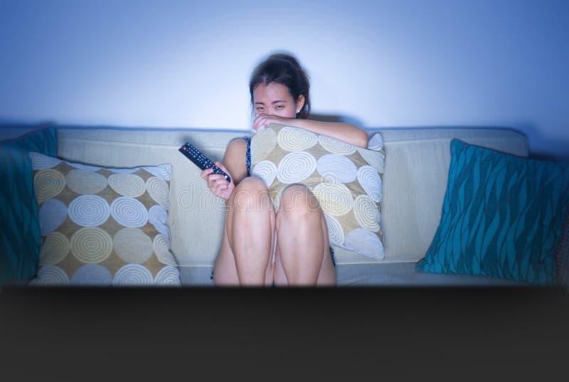 Mulher chinesa asiática nova assustado e do pânico em seu filme de terror 20s de observação na tevê que senta em casa o sofá do s imagens de stock