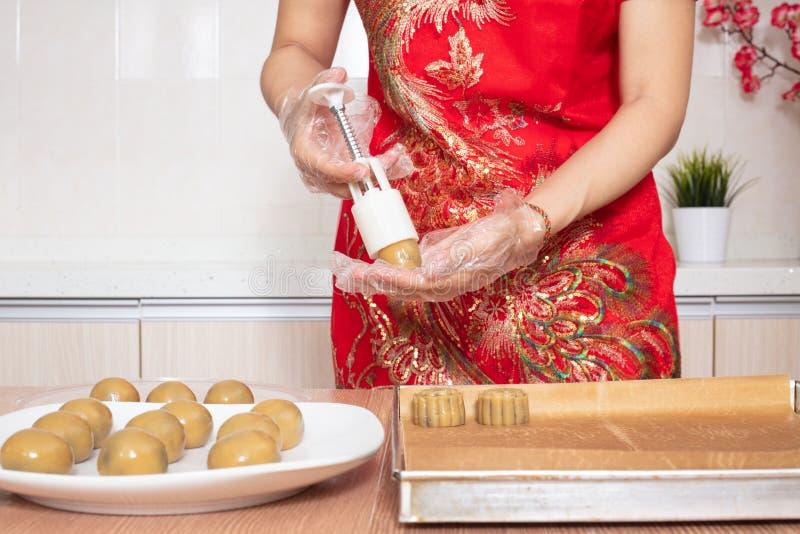 Mulher chinesa asiática que faz a lua endurecer na cozinha fotos de stock