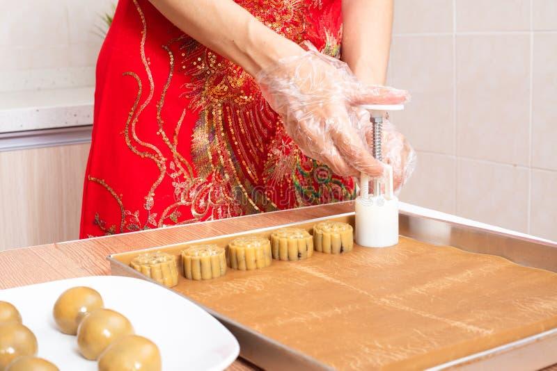 Mulher chinesa asiática que faz a lua endurecer na cozinha imagens de stock