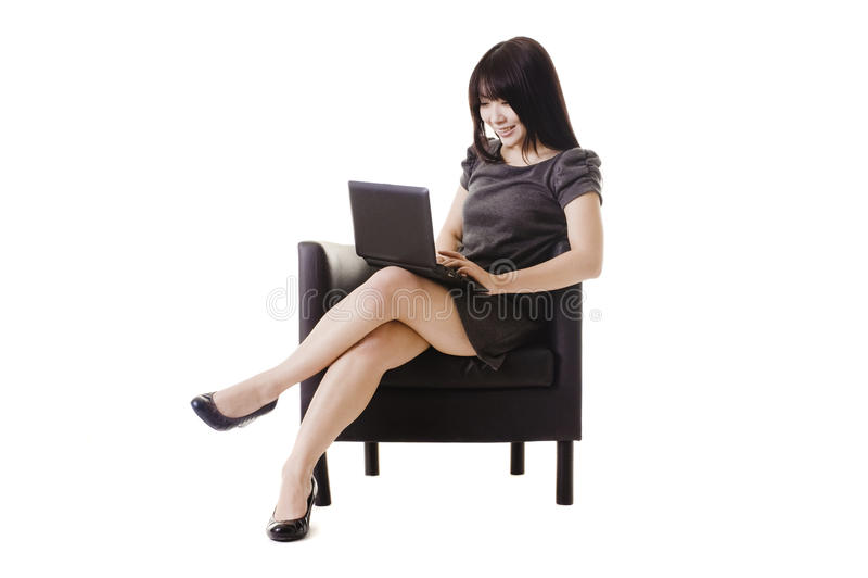 Mulher chinesa atrativa que trabalha em um netbook. imagem de stock
