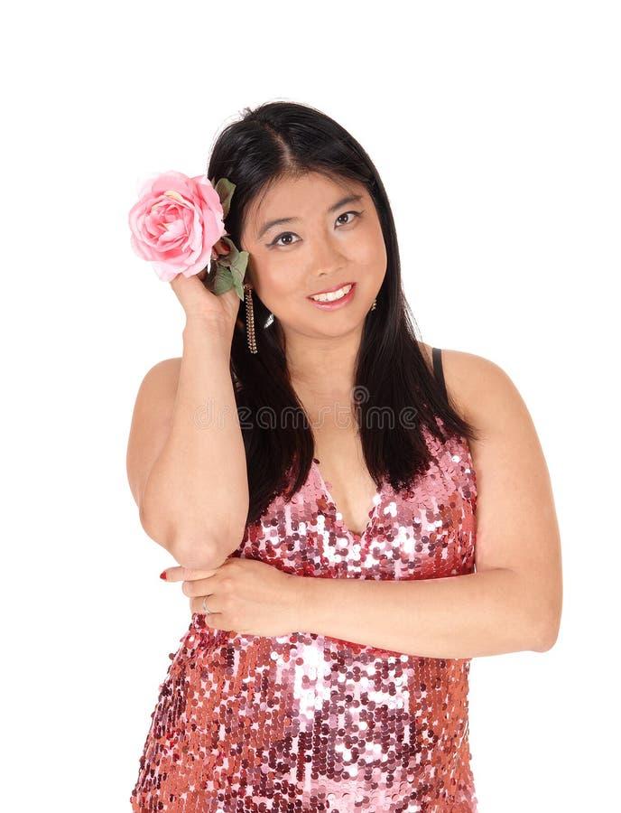 Mulher chinesa bonita que guarda uma rosa cor-de-rosa a seu cabelo imagens de stock royalty free