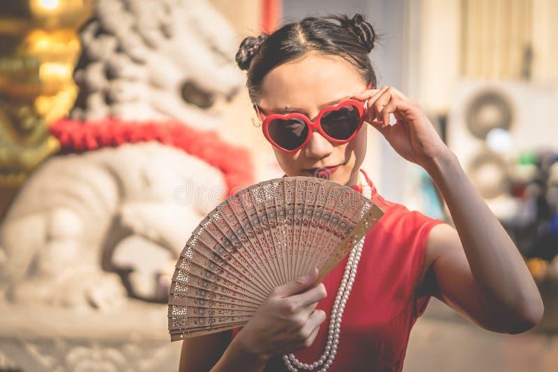 Mulher chinesa com os óculos de sol com o fã de madeira para o conceito chinês moderno da menina imagens de stock royalty free