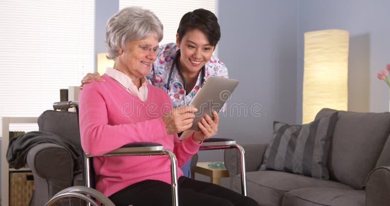 Mulher chinesa e paciente idoso que falam com tabuleta foto de stock royalty free