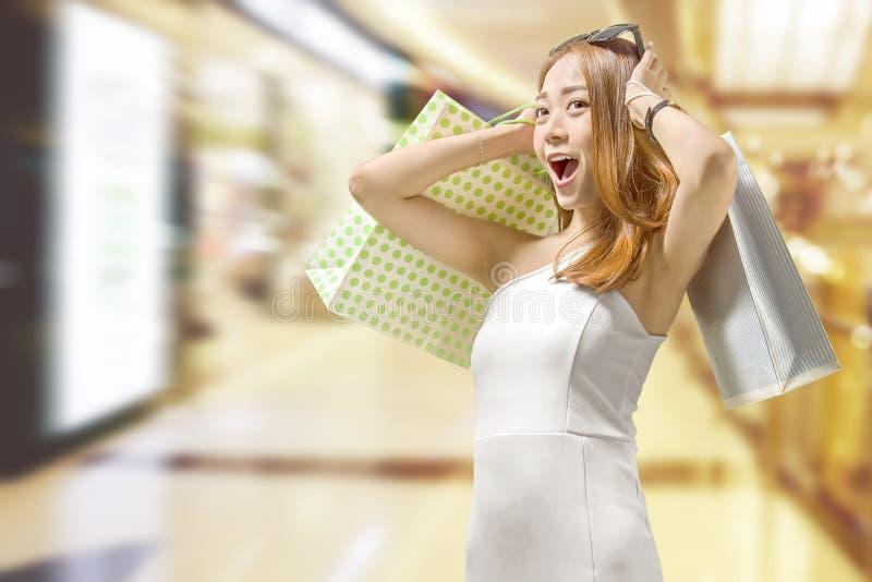 Mulher chinesa expressivo com os sacos de compras coloridos na alameda fotos de stock