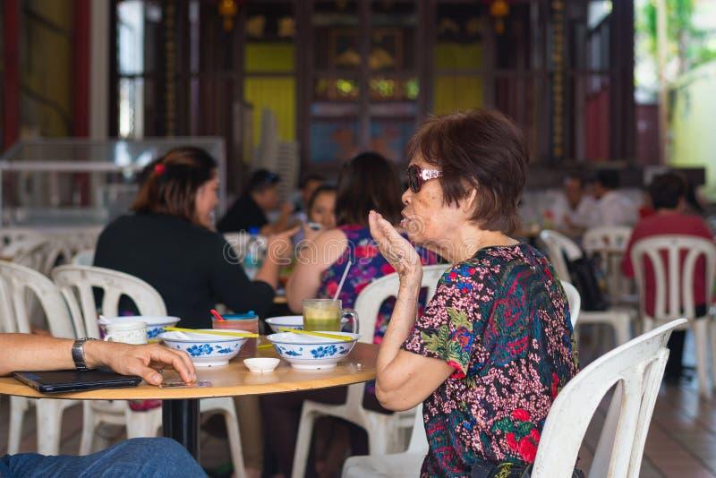 Mulher chinesa madura que janta na tenda do alimento imagens de stock
