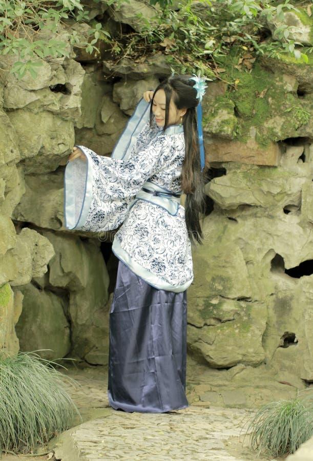 Mulher chinesa no vestido azul e branco tradicional de Hanfu que está na frente do jardim ornamental imagem de stock royalty free