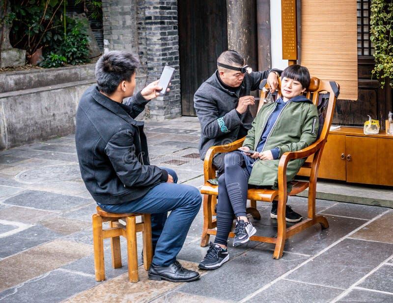 Mulher chinesa que faz a orelha-limpeza nas aleias largas e estreitas de Chengdu com seu noivo que toma imagens em China foto de stock royalty free
