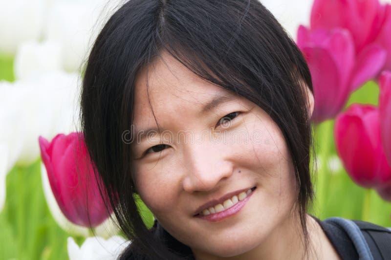 Mulher chinesa que sorri em um jardim da tulipa fotografia de stock