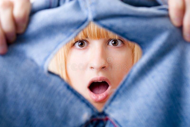 Mulher choc com calças de brim rasgadas imagem de stock