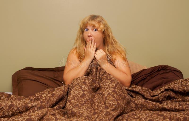 Mulher choc na cama fotos de stock