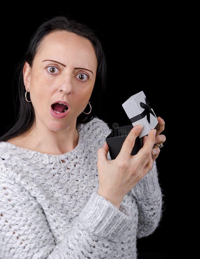 Mulher chocada após ter aberto o presente foto de stock