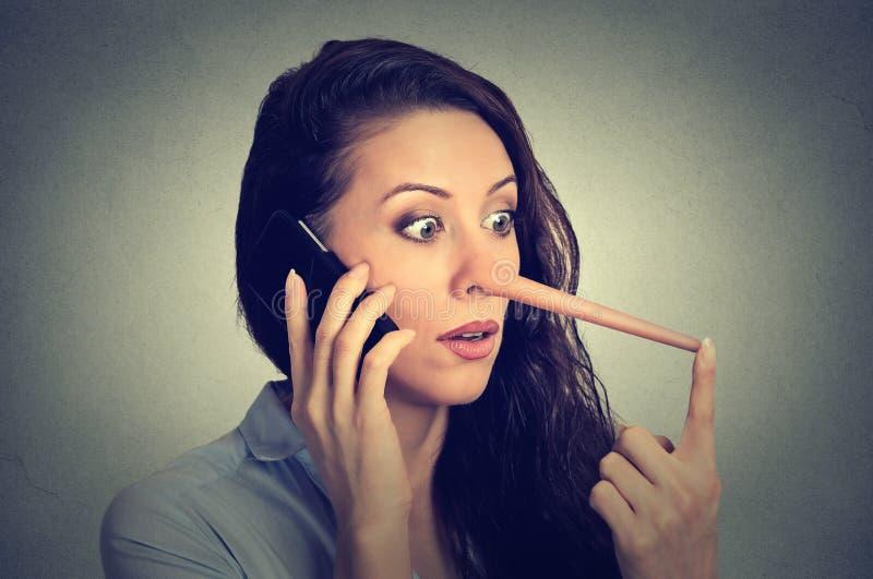 Mulher chocada com nariz longo que fala no telefone celular Conceito do mentiroso imagem de stock royalty free