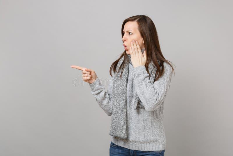 A mulher chocada na camiseta, vista do lenço, apontando o indicador de lado pôs a mão sobre o mordente no fundo cinzento imagens de stock royalty free