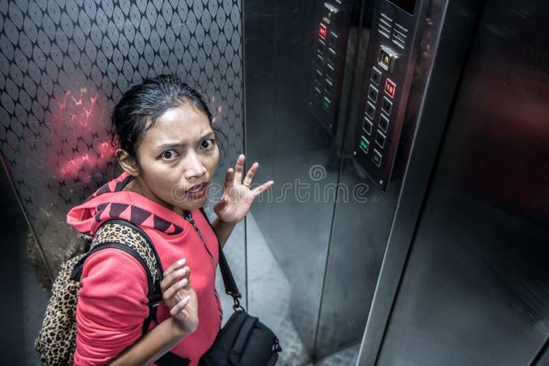 A mulher chocada no elevador movente imagem de stock royalty free