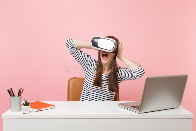 Mulher chocada nova nos auriculares da realidade virtual que aderem-se para dirigir gritar a sentar-se e trabalhar na mesa branca foto de stock royalty free