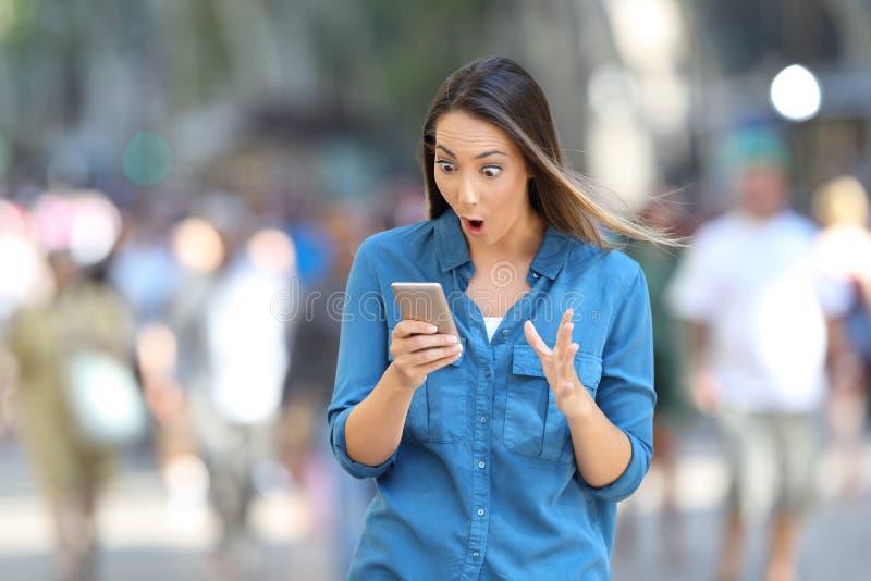 Mulher chocada que lê mensagens de telefone espertas foto de stock royalty free