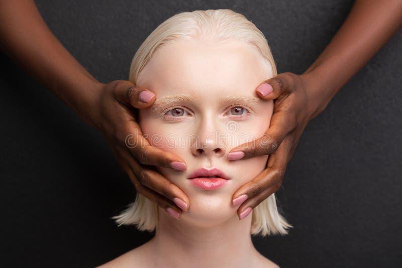 mulher Cinzento-eyed que tem as m?os de pele escura na cara fotografia de stock royalty free