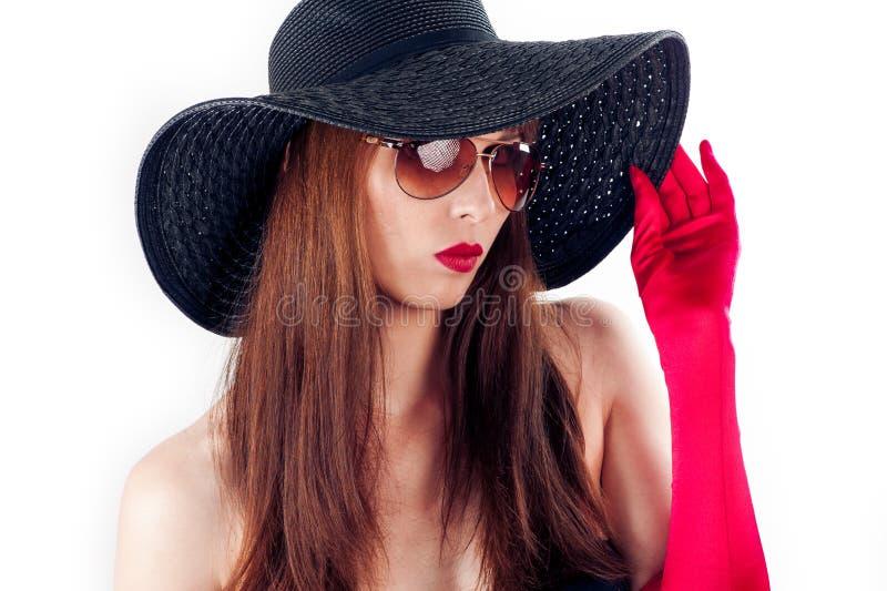 a mulher cobre sua cara com seu chapéu imagem de stock