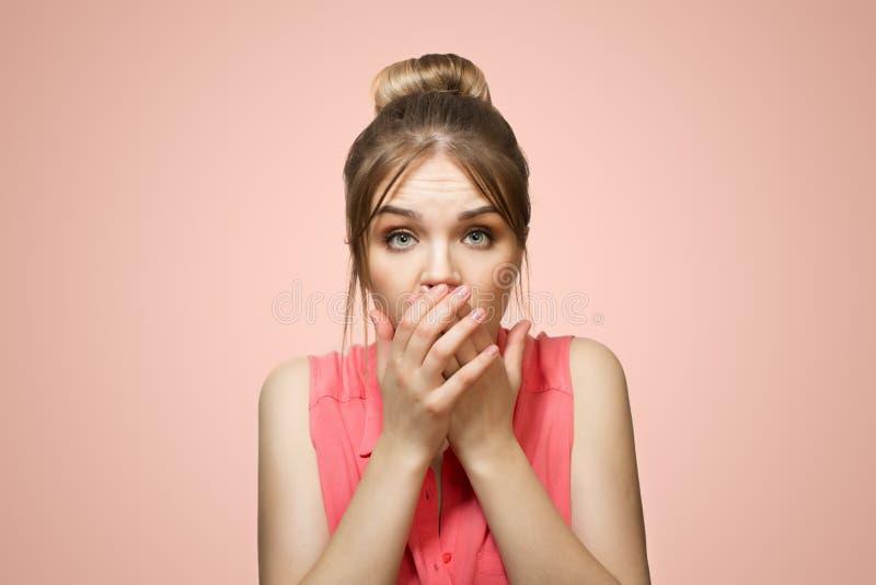 A mulher cobriu sua boca com suas mãos fotografia de stock royalty free
