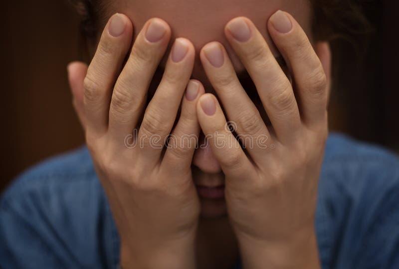A mulher cobriu sua cara com suas mãos fotos de stock