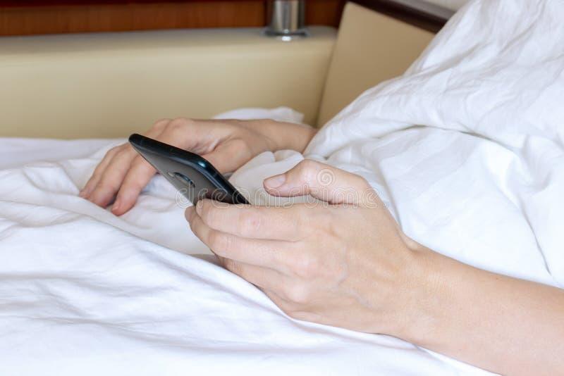 Mulher colhida que encontra-se na cama Menina bonita que usa o telefone celular e o descanso fotografia de stock