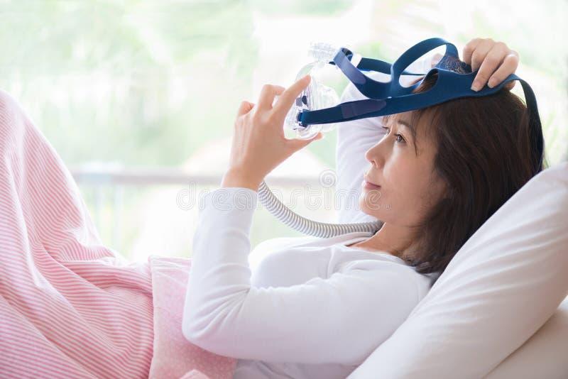 A mulher coloca na cama que veste a máscara de CPAP, terapia da apneia do sono fotografia de stock royalty free