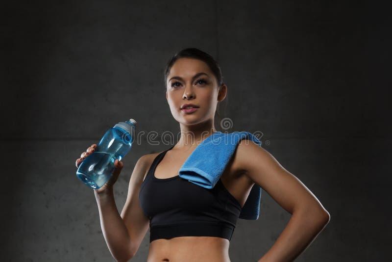 Mulher com água potável de toalha da garrafa no gym fotografia de stock