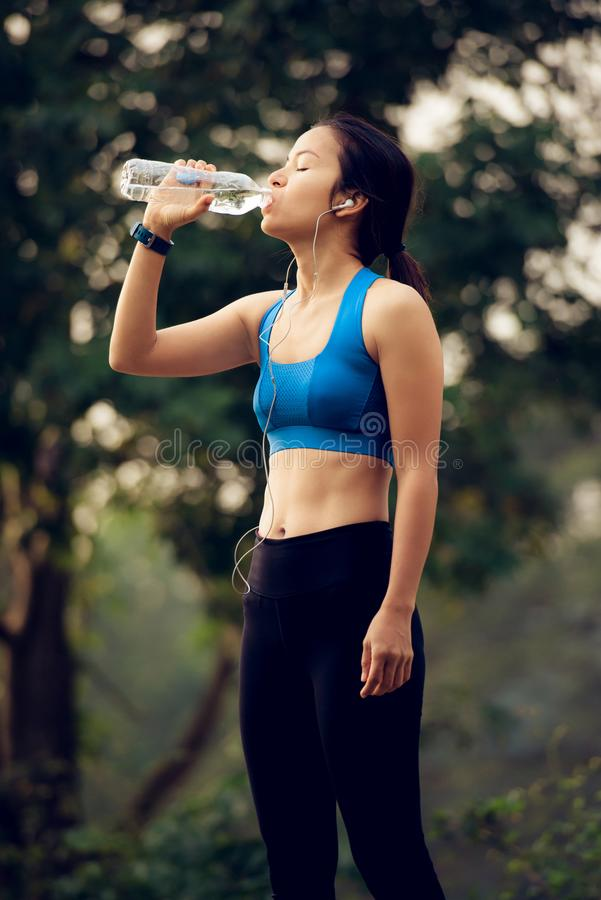 Mulher com água potável dos fones de ouvido após o exercício fotografia de stock royalty free