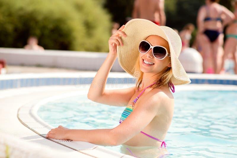 Mulher com óculos de sol e chapéu na piscina, água fotos de stock