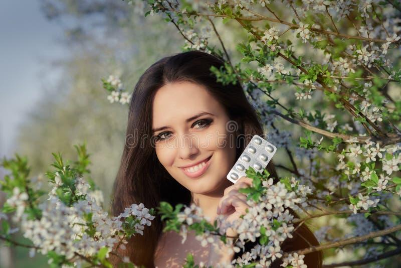Mulher com a alergia que guarda anti comprimidos alérgicos na decoração de florescência da mola imagens de stock royalty free