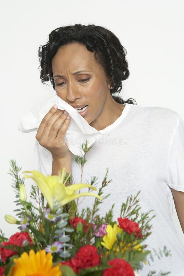 Mulher com a alergia que guarda o tecido perto das flores fotos de stock