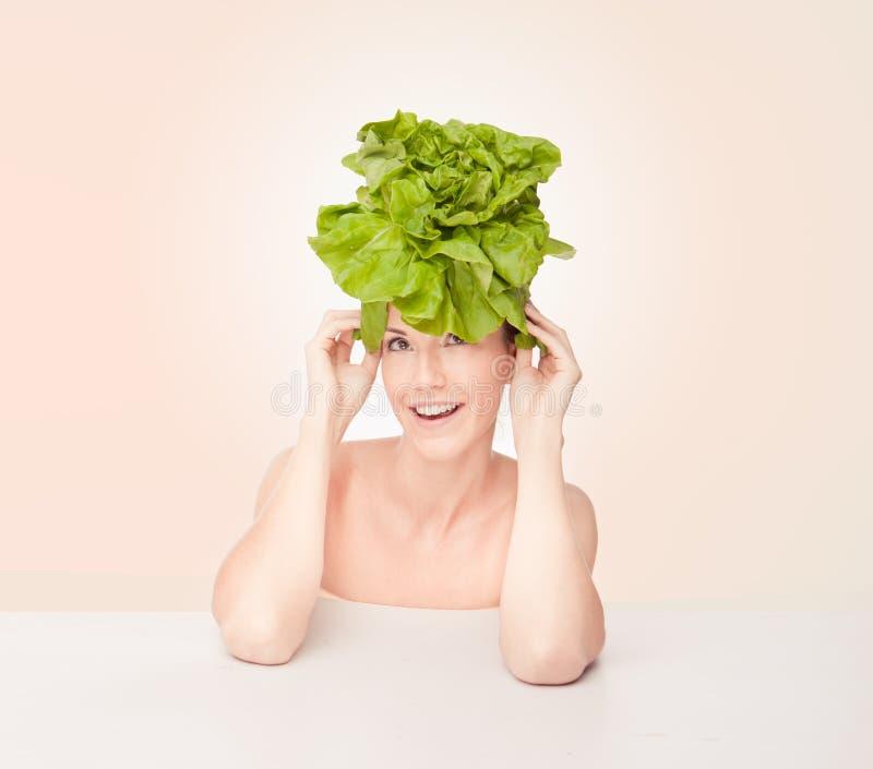 Mulher com alface na cabeça imagem de stock