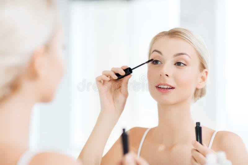 A mulher com aplicação do rímel compõe no banheiro imagens de stock royalty free