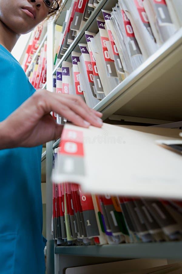 Mulher com arquivo em arquivos do hospital fotos de stock