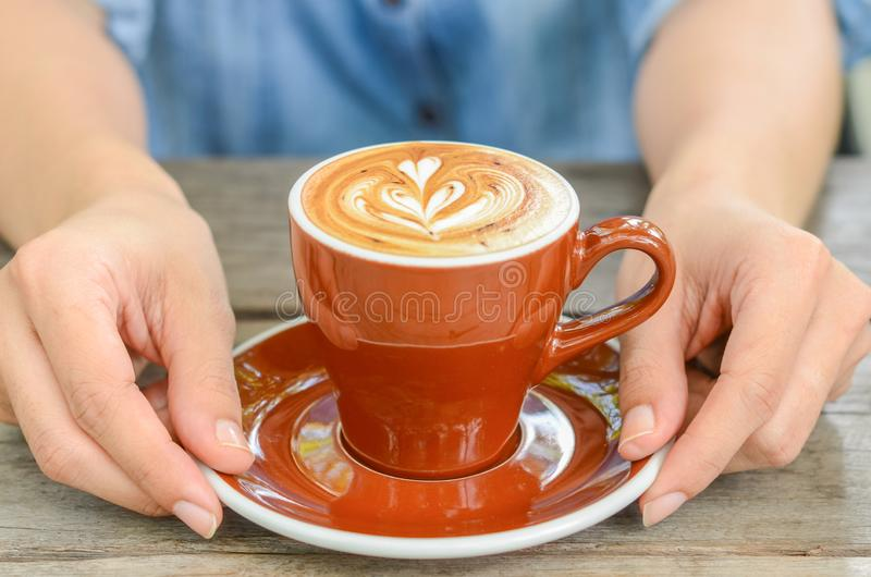 Mulher com arte do latte da xícara de café no café fotografia de stock