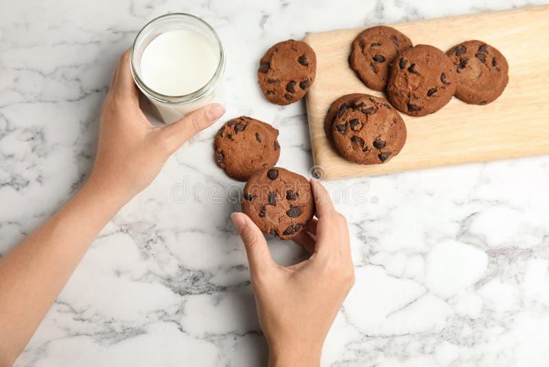 Mulher com as cookies saborosos e o leite dos pedaços de chocolate no fundo claro fotografia de stock royalty free