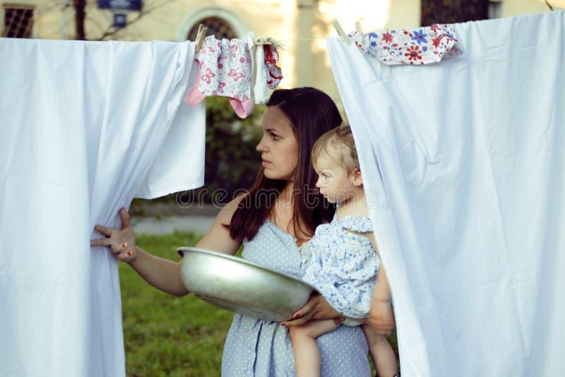 Mulher com as crianças na lavanderia de suspensão do jardim imagens de stock